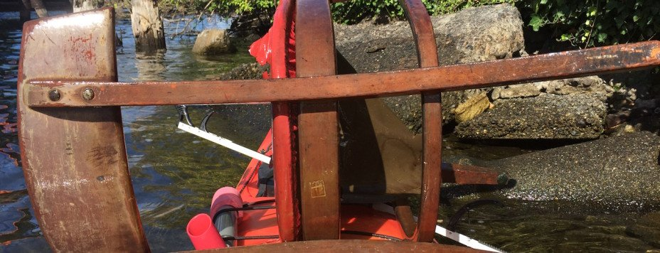 A chair retrieved from Lake Union, strapped to the front of a kayak.