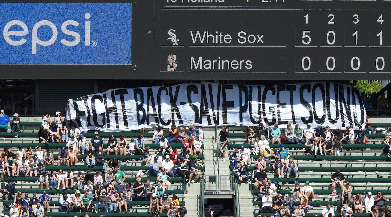 """A banner saying """"Fight Back - Protect Puget Sound"""" is held up at a Mariners game."""
