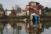 A sinking boathouse on the Duwamish River in front of a stack of cargo shipping containers.